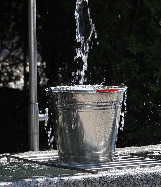 silver bucket sitting on a grate above a water trough with water trickling in. The water signifies competition entries and the bucket signifies how many of those a competition manages to capture.